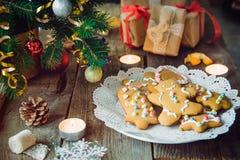 Fermez-vous vers le haut du plat avec les biscuits faits maison de pain d'épice sur la vieille table en bois rustique avec des bo Photo libre de droits