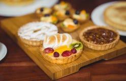 Fermez-vous vers le haut du plateau en bois des pâtisseries savoureuses Photos stock