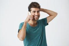 Fermez-vous vers le haut du portrait d'isolement du mâle espagnol de sourire dans le T-shirt à la mode, en souriant et en tenant  Image stock