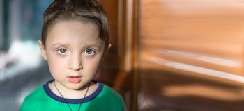 Fermez-vous vers le haut du portrait d'un bébé garçon européen étonné regardant l'appareil-photo au-dessus du fond clair Image libre de droits