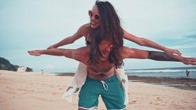 Fermez-vous vers le haut du portrait d'un jeune et énergique couple attrayant ayant l'amusement sur la plage Ferroutage de femme  banque de vidéos