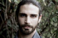 Fermez-vous vers le haut du portrait d'un jeune homme moderne avec la barbe et les longs cheveux Images stock