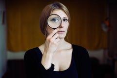 Fermez-vous vers le haut du portrait d'une belle femme avec une loupe en verre Photos libres de droits