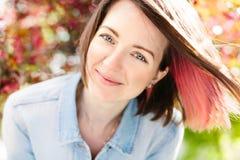 Fermez-vous vers le haut du portrait d'une belle fille avec les cheveux roses se tenant dans un jardin de floraison de pomme Ress Photographie stock libre de droits