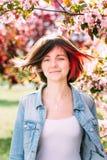 Fermez-vous vers le haut du portrait d'une belle fille avec les cheveux roses se tenant dans un jardin de floraison de pomme Ress Photos stock