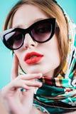 Fermez-vous vers le haut du portrait d'une belle fille dans les lunettes de soleil et l'écharpe dans le studio photo libre de droits