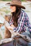 Fermez-vous vers le haut du portrait d'une cow-girl de sourire se penchant sur la barrière Photos stock