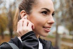 Fermez-vous vers le haut du portrait d'une fille heureuse de forme physique dans des écouteurs images stock