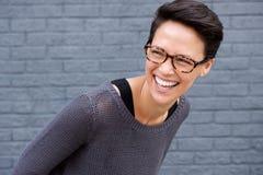 Fermez-vous vers le haut du portrait d'une jeune femme riant avec des verres Photo stock