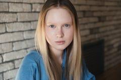Fermez-vous vers le haut du portrait d'une jeune fille blonde dans une chemise bleue Images libres de droits