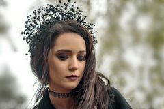 fermez-vous vers le haut du portrait d'une jeune fille dans l'image de la sorcière noire de reine dans un diadème noir de couronn photographie stock libre de droits