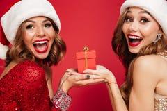 Fermez-vous vers le haut du portrait de deux femmes de sourire heureuses dans des chapeaux de Noël Images libres de droits