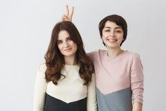 Fermez-vous vers le haut du portrait de jeunes paires lesbiennes heureuses avec les cheveux foncés dans des vêtements assortis so Image stock
