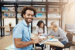 Fermez-vous vers le haut du portrait de l'étudiant noir-pelé bel s'asseyant sur la réunion avec des amis après étude, parlant Image stock
