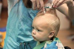 Fermez-vous vers le haut du portrait de l'enfant d'enfant en bas âge obtenant sa première coupe de cheveux images libres de droits
