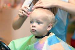 Fermez-vous vers le haut du portrait de l'enfant d'enfant en bas âge obtenant sa première coupe de cheveux photos libres de droits
