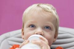 Fermez-vous vers le haut du portrait de l'enfant en bas âge aux yeux bleus buvant sa bouteille Photo libre de droits