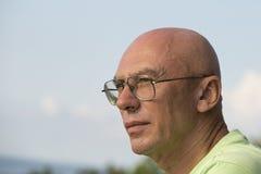 Fermez-vous vers le haut du portrait de l'homme d'une cinquantaine d'années détendant en nature Photographie stock libre de droits