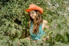 Fermez-vous vers le haut du portrait de la belle fille bouclée avec les cerises oranges de cueillette de chapeau de cowboy Images stock