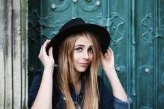 Fermez-vous vers le haut du portrait de la belle fille de sourire espiègle utilisant le chapeau noir à large bord élégant Looking Image libre de droits