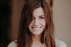 Fermez-vous vers le haut du portrait de la femme heureuse de brune avec le sourire toothy, regards heureusement à l'appareil-phot photographie stock libre de droits