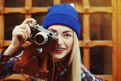 Fermez-vous vers le haut du portrait de la fille de sourire heureuse élégante de hippie dans les accolades avec le photocamera de Image stock