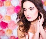 Fermez-vous vers le haut du portrait de la jeune belle femme au-dessus du backgrou de fleurs Photos stock