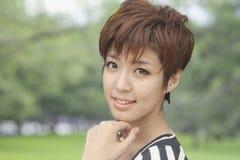Fermez-vous vers le haut du portrait de la jeune femme avec les cheveux courts souriant, dehors Photos libres de droits