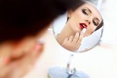 Fermez-vous vers le haut du portrait de la jeune femme avec les lèvres rouges. Belle femme faisant le maquillage quotidien. Photo libre de droits