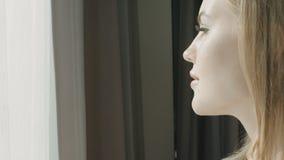 Fermez-vous vers le haut du portrait de la jeune femme blonde près de la fenêtre dans la chambre d'hôtel banque de vidéos