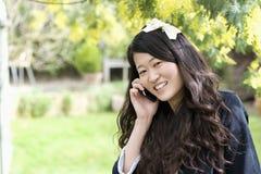 Fermez-vous vers le haut du portrait de la jeune femme parlant au téléphone portable Photos stock