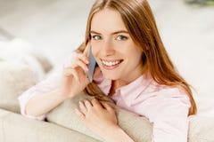 Fermez-vous vers le haut du portrait de la jeune fille attirante parlant au téléphone portable Photo libre de droits