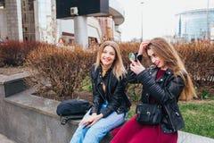 Fermez-vous vers le haut du portrait de mode de vie d'été de deux meilleurs amis riant et parlant extérieur sur la rue au centre  Photos libres de droits