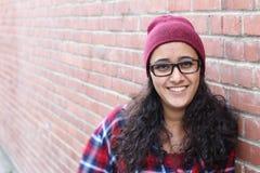 Fermez-vous vers le haut du portrait de studio de la fille gaie de hippie de brune faisant le visage heureux Fond urbain de mur d Photos stock