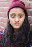 Fermez-vous vers le haut du portrait de studio de la fille gaie de hippie de brune faisant le visage heureux Fond urbain de mur d Photographie stock libre de droits