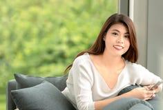 Fermez-vous vers le haut du portrait de tir de la jeune belle femme asiatique s'asseyant dessus images stock