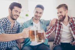 Fermez-vous vers le haut du portrait de trois amis heureux d'hommes, tintant avec des glas Images libres de droits