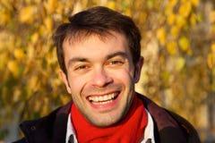 Fermez-vous vers le haut du portrait de visage d'un sourire de jeune homme Photos stock