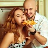 Fermez-vous vers le haut du portrait des couples ayant l'amusement avec la pizza Photo libre de droits