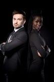 Fermez-vous vers le haut du portrait des couples ethniques multi sur le fond noir se tenant de nouveau au dos Image libre de droits