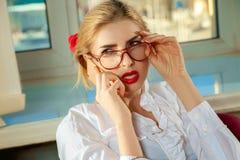 Fermez-vous vers le haut du portrait du téléphone parlant de secrétaire blond sexy Photo libre de droits