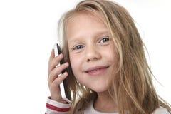 Fermez-vous vers le haut du portrait franc du bel enfant féminin avec les cheveux blonds et les yeux bleus utilisant parler de té photo stock