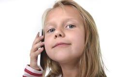Fermez-vous vers le haut du portrait franc du bel enfant féminin avec les cheveux blonds et les yeux bleus utilisant parler de té photographie stock
