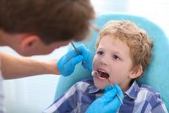 Fermez-vous vers le haut du portrait du garçon faisant examiner ses dents par un dentiste images libres de droits