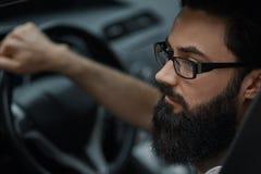 Fermez-vous vers le haut du portrait, homme sérieux conduisant une voiture image stock