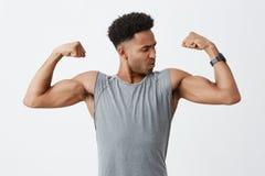 Fermez-vous vers le haut du portrait du jeune homme à la peau foncée sportif avec la coiffure Afro dans la chemise grise montrant Images libres de droits