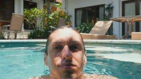 Fermez-vous vers le haut du portrait du jeune homme heureux beau détendant dans la piscine banque de vidéos