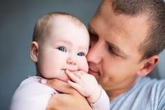 Fermez-vous vers le haut du portrait du jeune père embrassant le bébé à la maison Images stock
