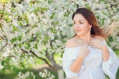 Fermez-vous vers le haut du portrait romantique de la belle femme élégante dans des arbres de ressort de fleur photos libres de droits