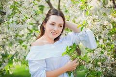 Fermez-vous vers le haut du portrait romantique de la belle femme élégante dans des arbres de ressort de fleur photographie stock libre de droits